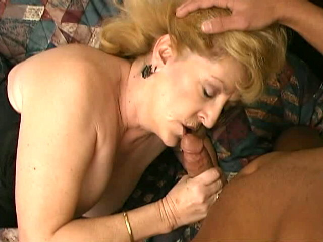 Uninhibited busty blonde granny Kitty Fox sucking a large black cock in bedroom